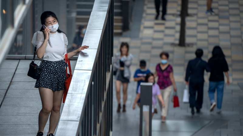 A woman wearing a face mask to prevent the spread of COVID-19 stands on a balcony as she talks on her cellphone at a shopping mall in Beijing, Saturday, July 17, 2021. (AP Photo/Mark Schiefelbein)