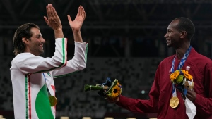 Joint gold medalists Mutaz Barshim, right, of Qatar, and Gianmarco Tamberi, left, of Italy celebrate on the podium following the men's high jump final at the 2020 Summer Olympics, Aug. 2, 2021, in Tokyo. (AP Photo/Francisco Seco)