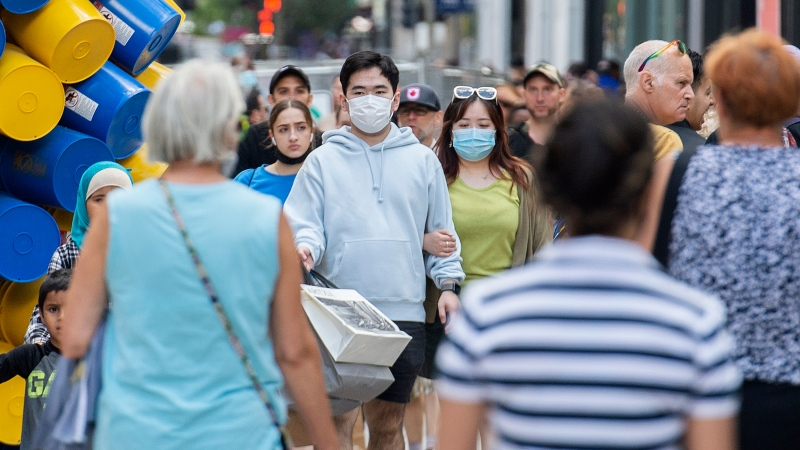 People wear face masks as they walk along a street in Montreal, Saturday, July 31, 2021, as the COVID-19 pandemic continues in Canada and around the world. THE CANADIAN PRESS/Graham Hughes
