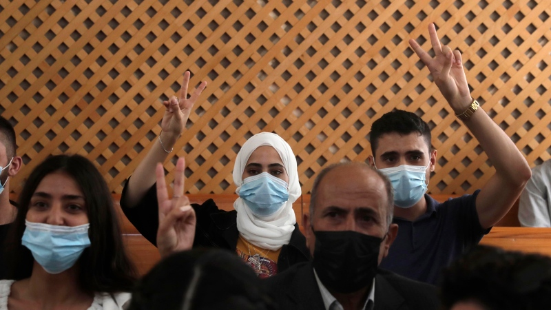 Palestinian residents of the Sheikh Jarrah neighbourhood in Jerusalem flash the victory sign prior to a hearing on possible evictions from their neighborhood, at the Supreme Court in Jerusalem, Monday, Aug. 2, 2021. (AP Photo/Maya Alleruzzo)