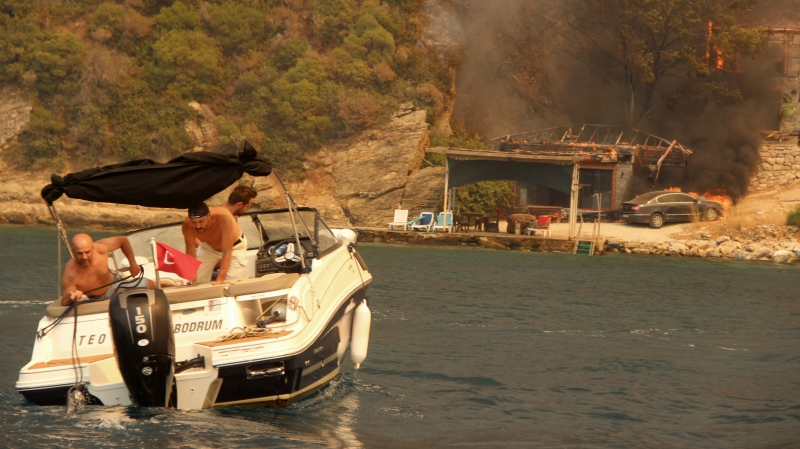 People use a boat to evacuate from smoke-engulfed Mazi area with a burning house and a car in the background, in Bodrum, Mugla, Turkey, Sunday, Aug. 1, 2021. (IHA via AP)