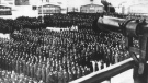 This undated file photo shows a roll call, in the early morning or late evening hours, on the roll call square in front of the camp gate of the Nazi concentration camp Sachsenhausen in Oranienburg on the outskirts of Berlin, Germany. In the foreground on the tower a machine gun pointed at the prisoners. A German court has set a trial date for a 100-year-old man who is charged with 3,518 counts of being an accessory to murder on allegations he served during World War II as a Nazi SS guard at the Sachenhausen camp. (AP Photo, file)