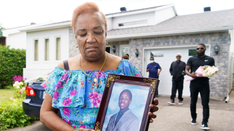 Marie-Mireille Bence, mother of Jean-Rene Jr. Olivier, who was shot dead by police, holds a picture of her son in front of the family home in Repentigny, Que. on Monday, August 2, 2021. THE CANADIAN PRESS/Paul Chiasson