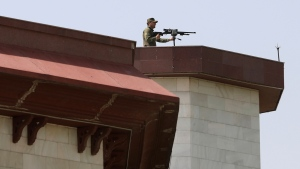 Rooftop security stands guard on the top of a Parliament building as President Ashraf Ghani helicopter lands at the Darul Aman Palace in Kabul, Afghanistan, Monday, Aug. 2, 2021. (AP Photo/Rahmat Gul)