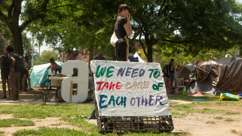 An encampment supporter waits for Toronto police to clear Lamport Stadium Park homeless encampment in Toronto, on Wednesday, July 21, 2021. (THE CANADIAN PRESS/Chris Young)