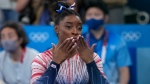 Simone Biles, of the United States, blows kisses after performing on the balance beam during the artistic gymnastics women's apparatus final at the 2020 Summer Olympics, Aug. 3, 2021, in Tokyo, Japan. (AP Photo/Ashley Landis)