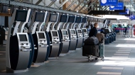 A traveller waits next to check-in kiosks not currently in use at Vancouver International Airport, in Richmond, B.C., on Friday, July 30, 2021. (Darryl Dyck / THE CANADIAN PRESS)