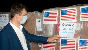 Veaceslav Gutu from the National Agency for Public Health adjusts a sticker that reads 'Covax' on boxes containing COVID-19 vaccines, at the Chisinau International Airport, in Chisinau, Moldova, Monday, July 12, 2021. AP Photo/Nadejda Roscovanu)