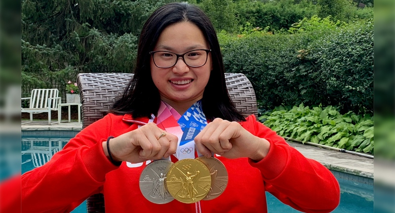 Maggie Mac Neil holds up her medals from the Tokyo Games back home in London, Ont. on Tuesday, Aug. 5, 2021. (Brent Lale / CTV News)