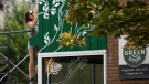 Emily Beckman paints the mural above the windows of the Green Door Restaurant in Ottawa, on Tuesday, Aug. 3, 2021. (Justin Tang/THE CANADIAN PRESS)