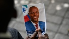 A person holds a photo of late Haitian President Jovenel Moise during his memorial ceremony at the National Pantheon Museum in Port-au-Prince, Haiti, Tuesday, July 20, 2021. Moise was assassinated at home on July 7. (AP Photo/Matias Delacroix)