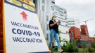 A woman wears a face mask as she walks by a COVID-19 vaccination sign in Montreal, Sunday, August 1, 2021, as the COVID-19 pandemic continues in Canada and around the world. (THE CANADIAN PRESS/Graham Hughes)