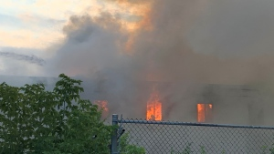 Smoke and flame can be seen at a fire on Centre Street in London, Ont. on Tuesday, Aug. 3, 2021. (Bryan Bicknell / CTV News)