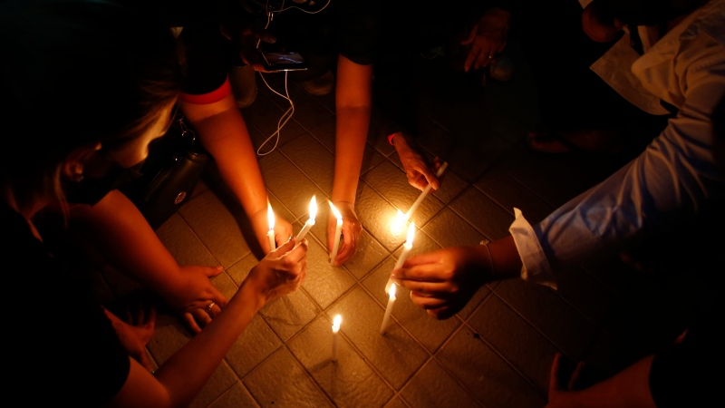 Pro-democracy supporters light candle during a protest in Bangkok, Thailand, Tuesday, Aug. 3, 2021. (AP Photo/Anuthep Cheysakron)