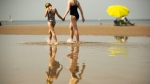 Beach goers walk along the shore during a hot summer day at the beach in De Haan, Belgium, Thursday, July 25, 2019. (AP Photo/Francisco Seco)