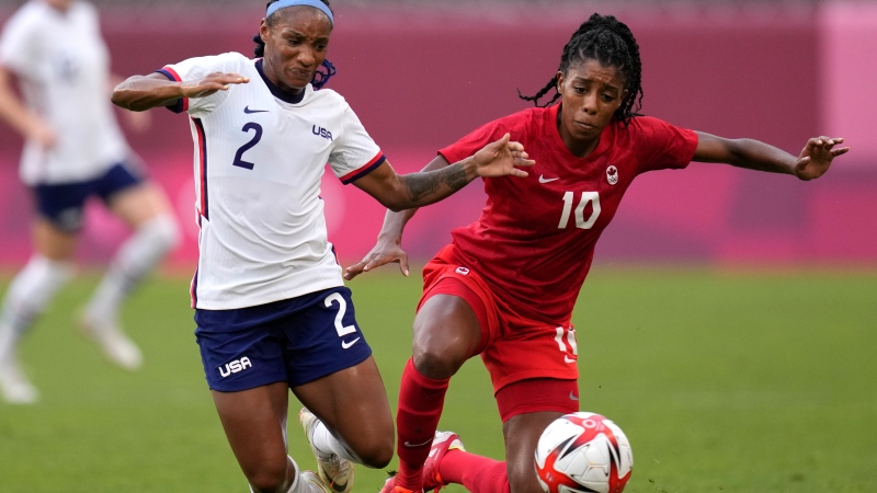 United States' Crystal Dunn, left, and Canada's Ashley Lawrence battle for the ball during a women's semifinal soccer match at the 2020 Summer Olympics, Aug. 2, 2021, in Kashima, Japan. (AP Photo/Andre Penner)