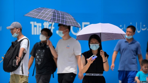 Visitors wear face masks to protect against COVID-19 as they walk at a tourist shopping street in Beijing, Tuesday, Aug. 3, 2021. (AP Photo/Mark Schiefelbein)