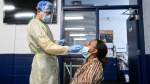 A health-care worker tests a woman at a pop-up COVID-19 assessment centre at the Angela James Arena during the COVID-19 pandemic in Toronto May 19, 2021. THE CANADIAN PRESS/Nathan Denette