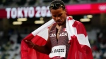 Canada's Andre De Grasse wraps himself in a Canadian flag after racing to a gold medal in the men's 200m final during the Tokyo Olympics in Japan, August 4, 2021. THE CANADIAN PRESS/Frank Gunn
