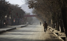 An Afghan man rides his bicycle on an empty street in Kabul, Afghanistan, Thursday, Nov. 19, 2009. The Afghan capital is under heavy security Thursday for the inauguration of Afghan President Hamid Karzai. (AP / Anja Niedringhaus)