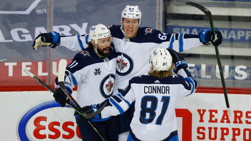 Winnipeg Jets' Logan Stanley (64) celebrates his goal with teammates Nate Thompson (11) and Kyle Connor during second period NHL hockey action against the Calgary Flames, in Calgary, Alta., Saturday, March 27, 2021. THE CANADIAN PRESS/Todd Korol