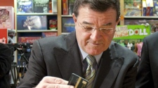 Finance Minister Jim Flaherty makes a purchase at Mrs. Tiggy Winkles toy store before making an announcement regarding credit and debit card conduct in Ottawa, Ont., on Thursday Nov. 19, 2009. (Sean Kilpatrick / THE CANADIAN PRESS)