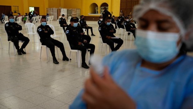 Police wait to be inoculated with the Moderna COVID-19 vaccine at a vaccination center in San Juan Sacatepequez, Guatemala, Thursday, July 15, 2021. (AP Photo/Moises Castillo)