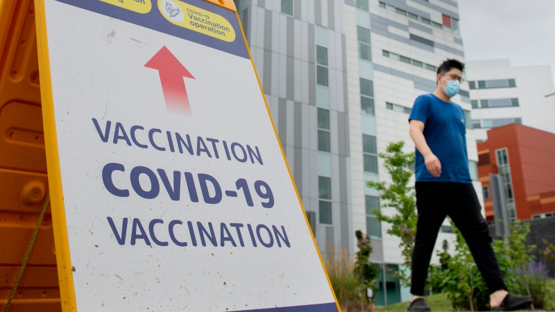 A man wears a face mask as he walks by a COVID-19 vaccination sign in Montreal, Sunday, August 1, 2021, as the COVID-19 pandemic continues in Canada and around the world. THE CANADIAN PRESS/Graham Hughes