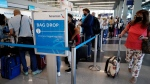 Travellers line up at O'Hare International Airport in Chicago, Friday, July 2, 2021. (AP Photo/Nam Y. Huh)