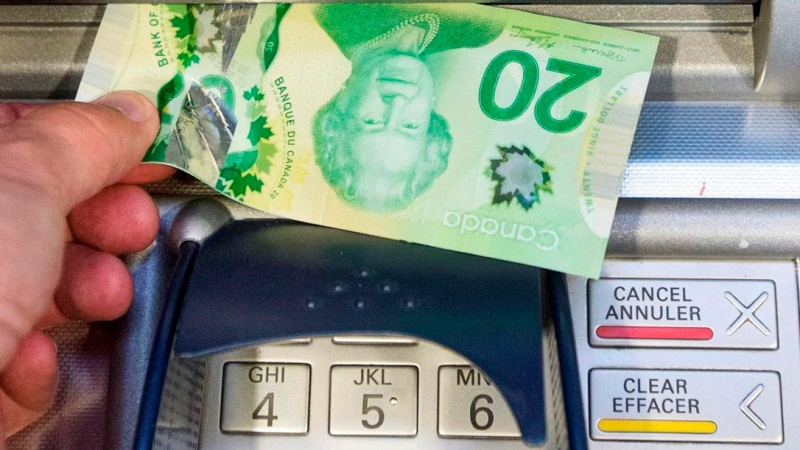 Money is removed from a bank machine in Montreal, Monday, May 30, 2016. Ryan Remiorz / THE CANADIAN PRESS