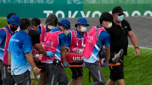 Medics carry away on a stretcher Connor Fields of the United States after he crashed at the first bend in the men's BMX Racing semifinals at the 2020 Summer Olympics, July 30, 2021, in Tokyo, Japan. (AP Photo/Ben Curtis)