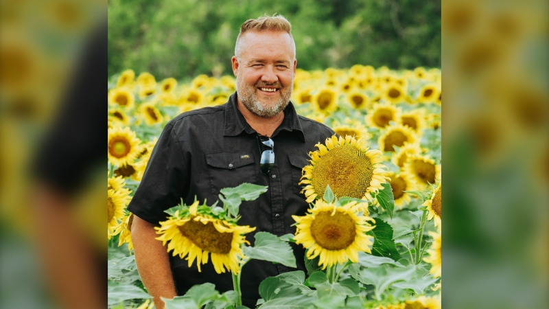 Dean Toews (pictured), who runs the farm with his family, opened up his sunflower field to raise awareness for the Canadian Foodgrains Bank. (Source: Kamp Photography)