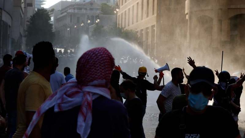 Riot police use tear gas and water cannon against anti-government protesters during a protest marking the first anniversary of the massive blast at Beirut's port, near Parliament Square, In Beirut, Lebanon, Wednesday, Aug. 4, 2021. (AP Photo/Bilal Hussein)