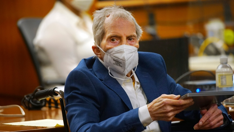 Robert Durst holds a device to read the real time spoken script as he appears in the courtroom of Judge Mark E. Windham as attorney's begin opening statements in the trial of the real estate scion charged with murder of longtime friend Susan Berman, at Los Angeles County Superior Court, Tuesday, May 18, 2021, in Inglewood, Calif. (Al Seib/Los Angeles Times via AP, Pool)