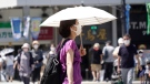 A woman wearing a face mask to curb the spread of the coronavirus walks with a parasol on a street in Tokyo Thursday, Aug. 5, 2021. (AP Photo/Kantaro Komiya)