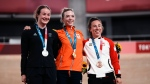 Gold medalist Shanne Braspennincx of Team Netherlands celebrates on the podium with silver medalist Ellesse Andrews of Team New Zealand and bronze medalist Lauriane Genest of Team Canada, during a medal ceremony for the track cycling women's keirin at the 2020 Summer Olympics, Aug. 5, 2021, in Izu, Japan. (AP Photo/Thibault Camus)