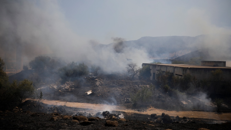 Fields burn following a hit by a rocket fired from Lebanon into Israeli territory, near the northern Israeli town of Kiryat Shmona, Wednesday, Aug. 4, 2021. Three rockets were fired from Lebanon into Israeli territory Wednesday and the army responded with sustained artillery fire, Israel's military said. There was no immediate information on damages or casualties. (AP Photo/Ariel Schalit)