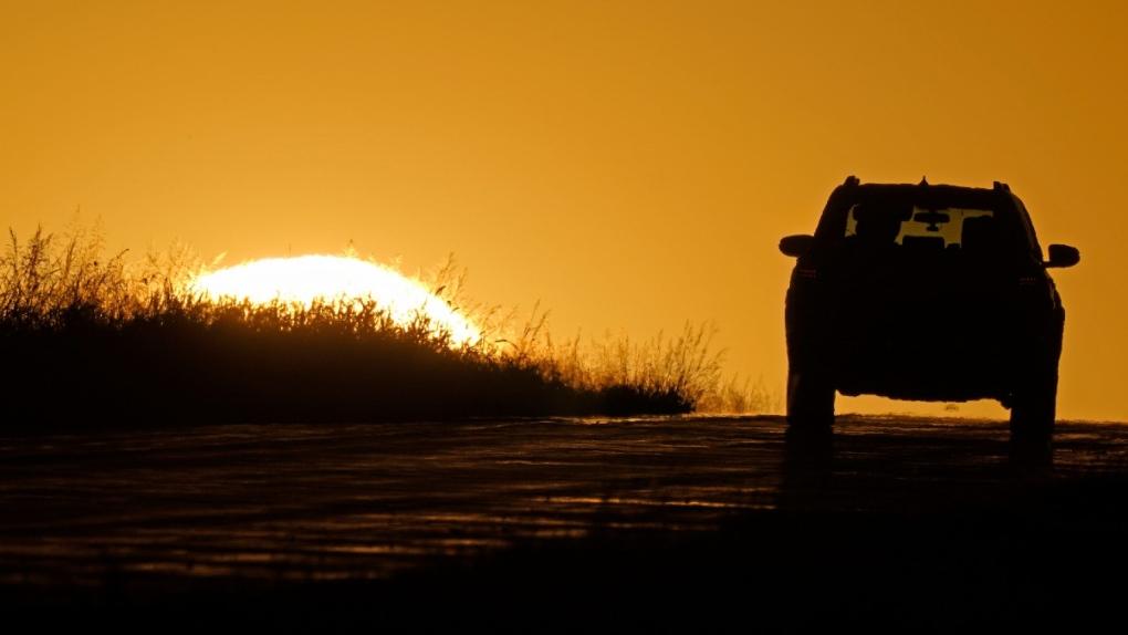 A motorist drives into the sunrise
