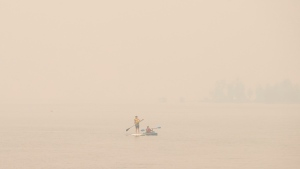 Wildfire smoke fills the air and obstructs the view of the mountains as people continue to take part in outdoor activities even though the air is currently 18 times above WHO exposure recommendation, in Sicamous B.C., on Thursday July 29, 2021. THE CANADIAN PRESS/Jason Franson