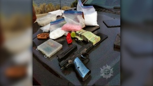 Seized weapons, drugs and cash are seen on the hood of a police vehicle following a traffic stop in the Kelowna, B.C., area on Aug. 4, 2021. (Handout)