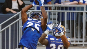 Winnipeg Blue Bombers' Josh Miller (25) and Brady Oliveira (20) go up for the pass during a warmup prior to their CFL game against the Hamilton Tiger-Cats in Winnipeg Thursday, August 5, 2021. THE CANADIAN PRESS/John Woods