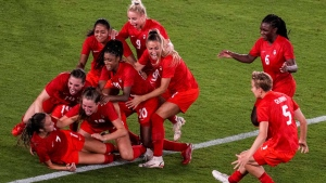 Teammates celebrate with Canada's Julia Grosso after she scored the winning goal against Sweden in the women's soccer match for the gold medal at the 2020 Summer Olympics, Friday, Aug. 6, 2021, in Yokohama, Japan. (AP Photo/Kiichiro Sato)