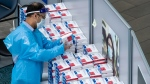 A worker picks up a COVID-19 self collection test kit which are given to arriving international passengers at Vancouver International Airport, in Richmond, B.C., on Friday, July 30, 2021. THE CANADIAN PRESS/Darryl Dyck