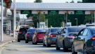 A line of vehicles wait to enter Canada at the Peace Arch border crossing Monday, Aug. 9, 2021, in Blaine, Wash. (AP Photo/Elaine Thompson)
