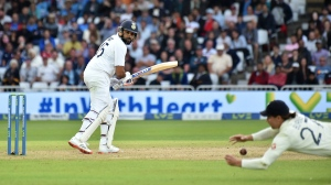 England's Rory Burns, right, dives to field the ball after a shot played by India's Rohit Sharma, left, during the fourth day of first test cricket match between England and India, at Trent Bridge in Nottingham, England, Saturday, Aug. 7, 2021. (AP Photo/Rui Vieira)