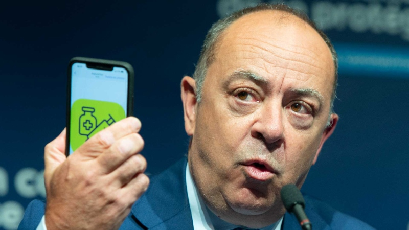 Quebec Health Minister Christian Dube shows an app on his phone as he announces details of the COVID-19 vaccination passport during a news conference Tuesday, August 10, 2021 in Montreal. THE CANADIAN PRESS/Ryan Remiorz