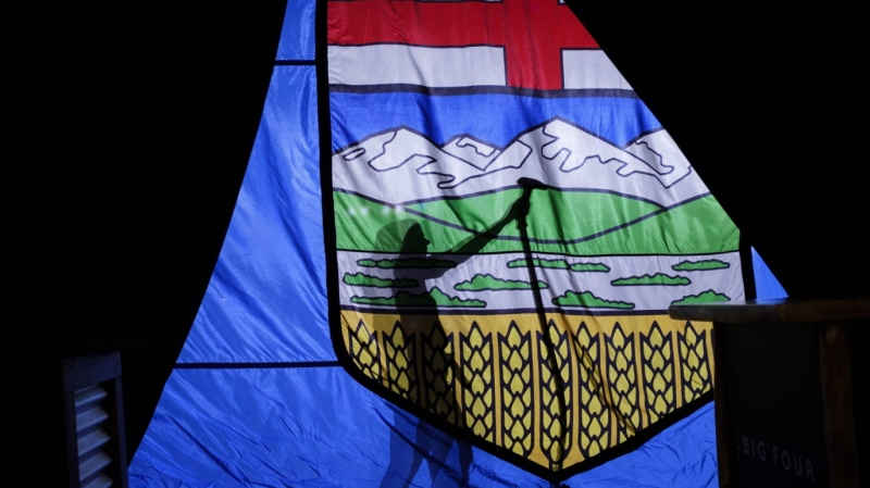 A campaign worker steams the wrinkles from a large Alberta flag in Calgary, Alta., Tuesday, April 16, 2019.THE CANADIAN PRESS/Jeff McIntosh