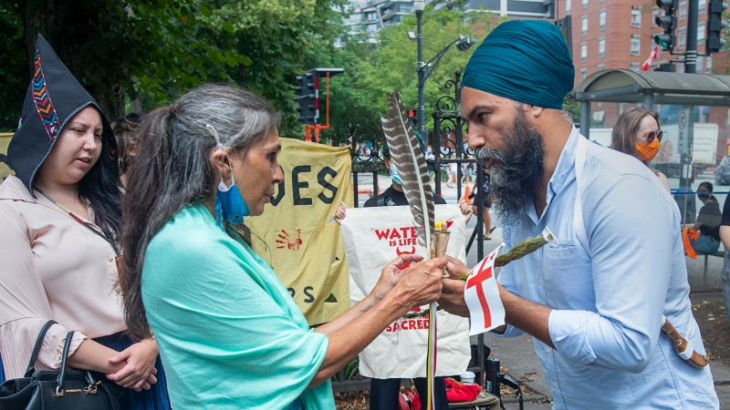Federal NDP Leader Jagmeet Singh talks with Thunderbird Swooping Down Woman, an Indigenous activist, during a visit to Halifax on Wednesday, Aug. 11, 2021. (THE CANADIAN PRESS/Andrew Vaughan)