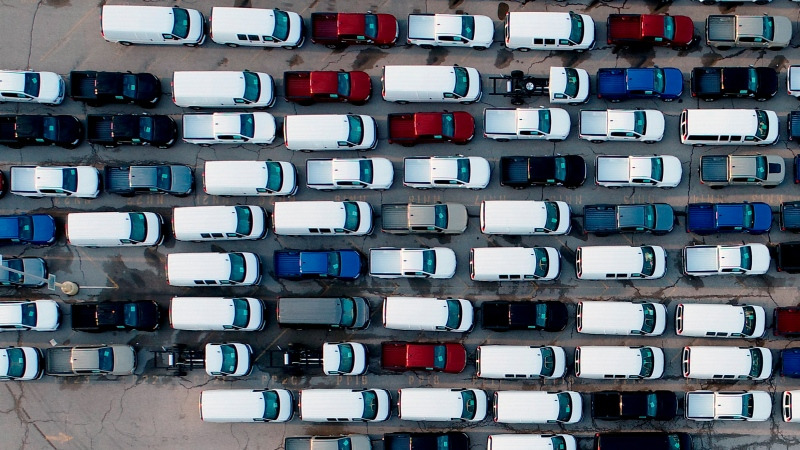 In this aerial photo, mid-sized pickup trucks and full-size vans are seen in a parking lot outside a General Motors assembly plant where they are produced Wednesday, March 24, 2021, in Wentzville, Mo. (AP Photo/Jeff Roberson)