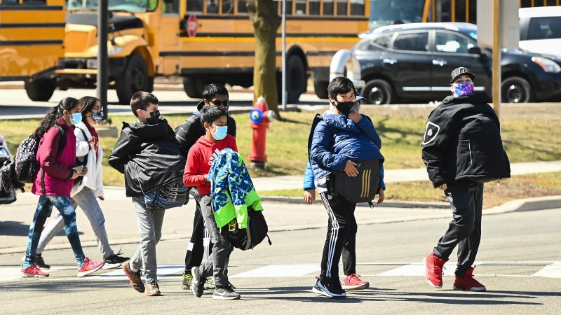 Students cross the street at Tomken Road Middle School during the COVID-19 pandemic in Mississauga, Ont., on Thursday, April 1, 2021. THE CANADIAN PRESS/Nathan Denette